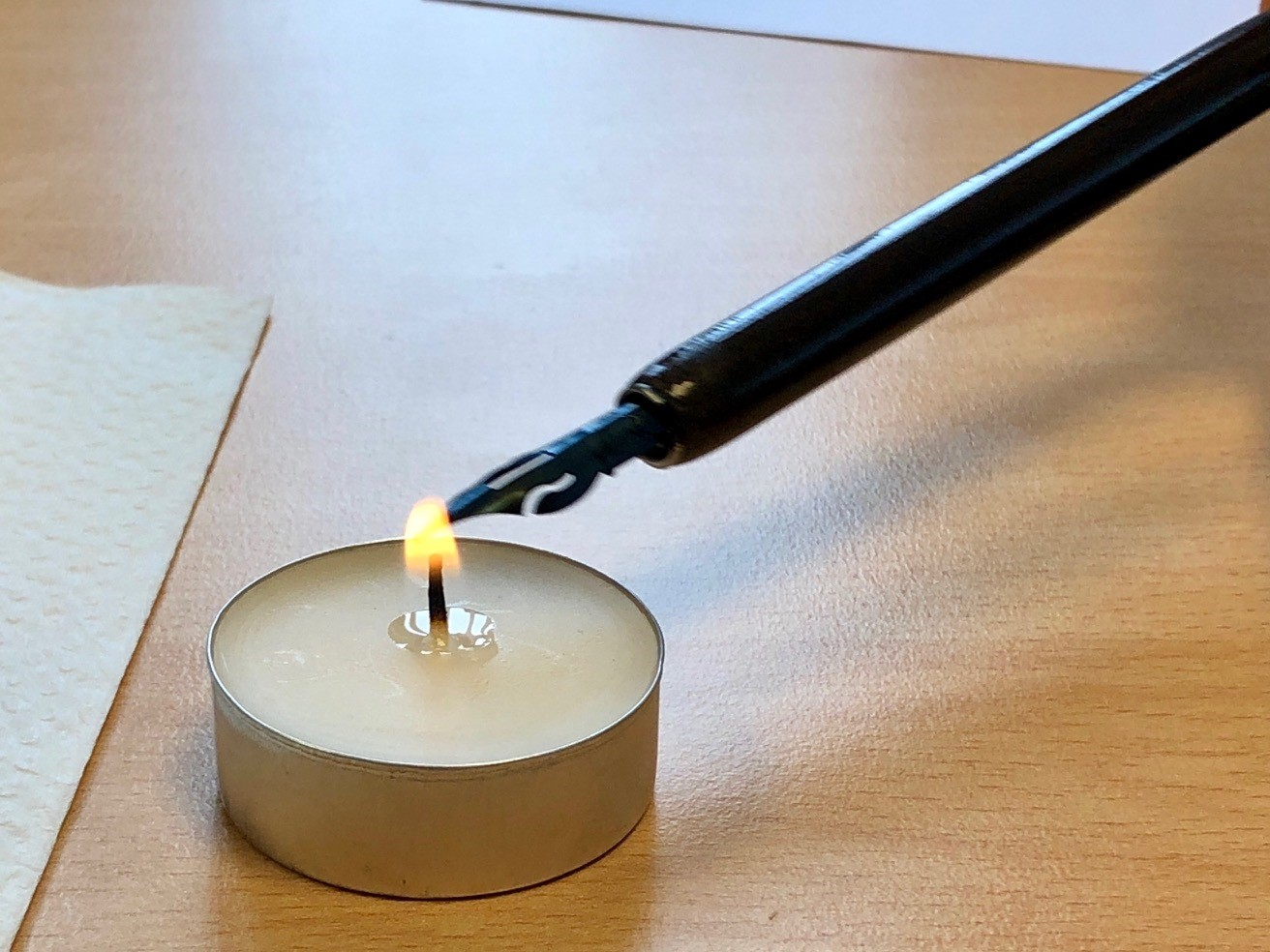 A candle flame being used to burn oils off a new nib